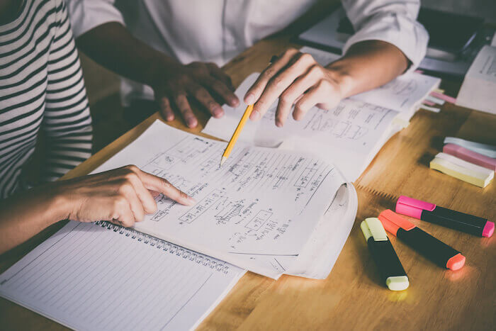 High school or college student group catching up workbook and learning tutoring in classroom and reading, doing homework and lesson practice preparing exam