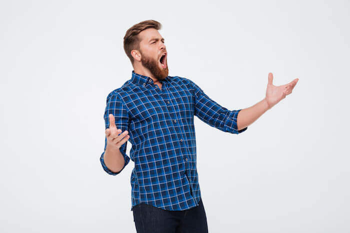 Young attractive bearded man singing loud